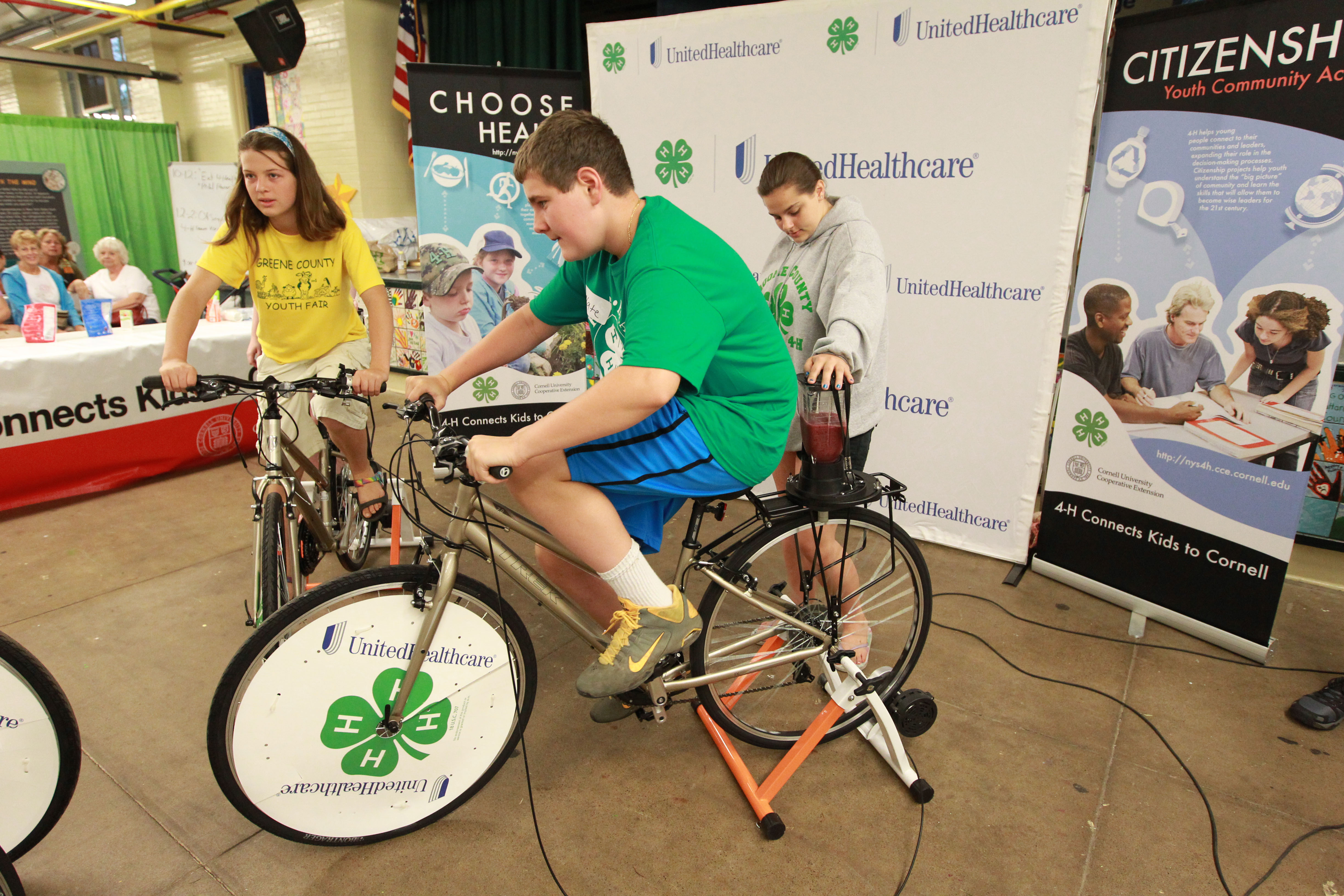 """4-H Youth Health Ambassadors Zaia Ivan from Greene, N.Y. (left), and Nate Edwards from Morris, N.Y. (center), create their own smoothies using pedal power at the annual New York State Fair in Geddes, near Syracuse, on Aug. 21. The smoothie bikes are part of 4-H and UnitedHealthcare's partnership called """"Eat4-Health,"""" which helps tackle obesity by promoting healthy eating and lifestyles among youth and families (Photo: Michael J. Okoniewski for UnitedHealthcare)."""