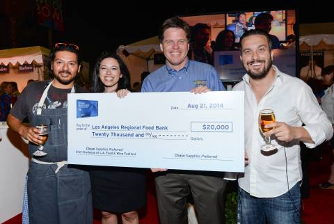 Chef Ray Garcia, left, Lauren Furgione, Vice President of Chase Sapphire, Michael Flood, President and CEO of Los Angeles Regional Food Bank, and Chef Fabio Viviani are awarded a $20,000 donation for Los Angeles Regional Food Bank at the Chase Sapphire Preferred Chef Challenge during the Ultimate Bites of L.A. at the Los Angeles Food & Wine Festival, presented by FOOD & WINE, on Thursday, Aug. 21, 2014 in Los Angeles. (Photo by Evan Agostini/Invision for Chase Sapphire Preferred/AP Images)