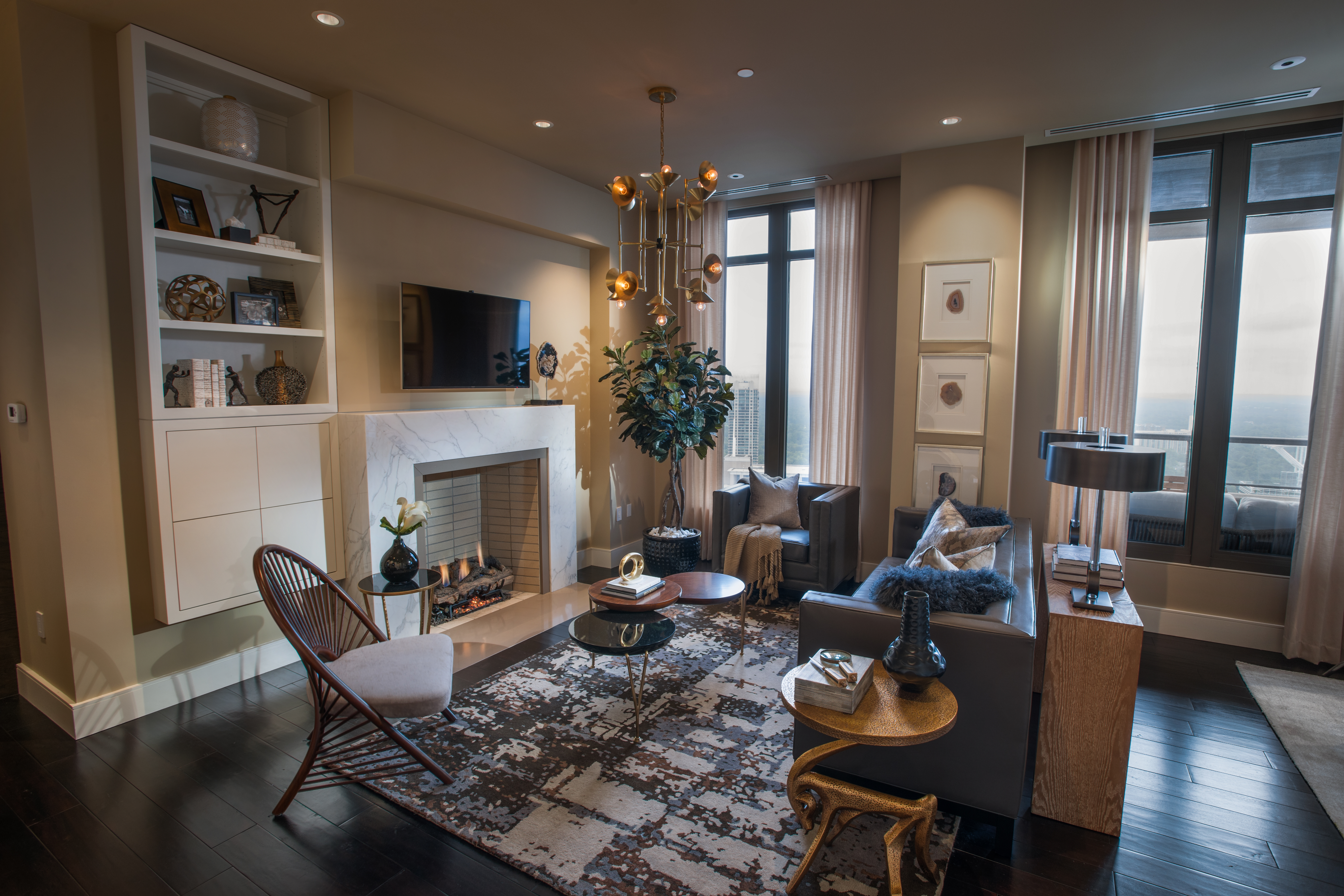 Inspired by the property's high-end design, refined modern elegance is showcased in the living room with black and gold finishes, custom-built shelving and Carrara marble surrounding the gas fireplace. (Photo: Business Wire)