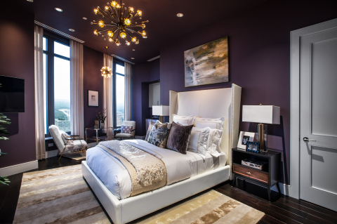 The master bedroom is dressed with a dramatic plum wall color layered with luxe furnishings in hues of gold and ivory, evoking modern elegance and glamour.(Photo: Business Wire)