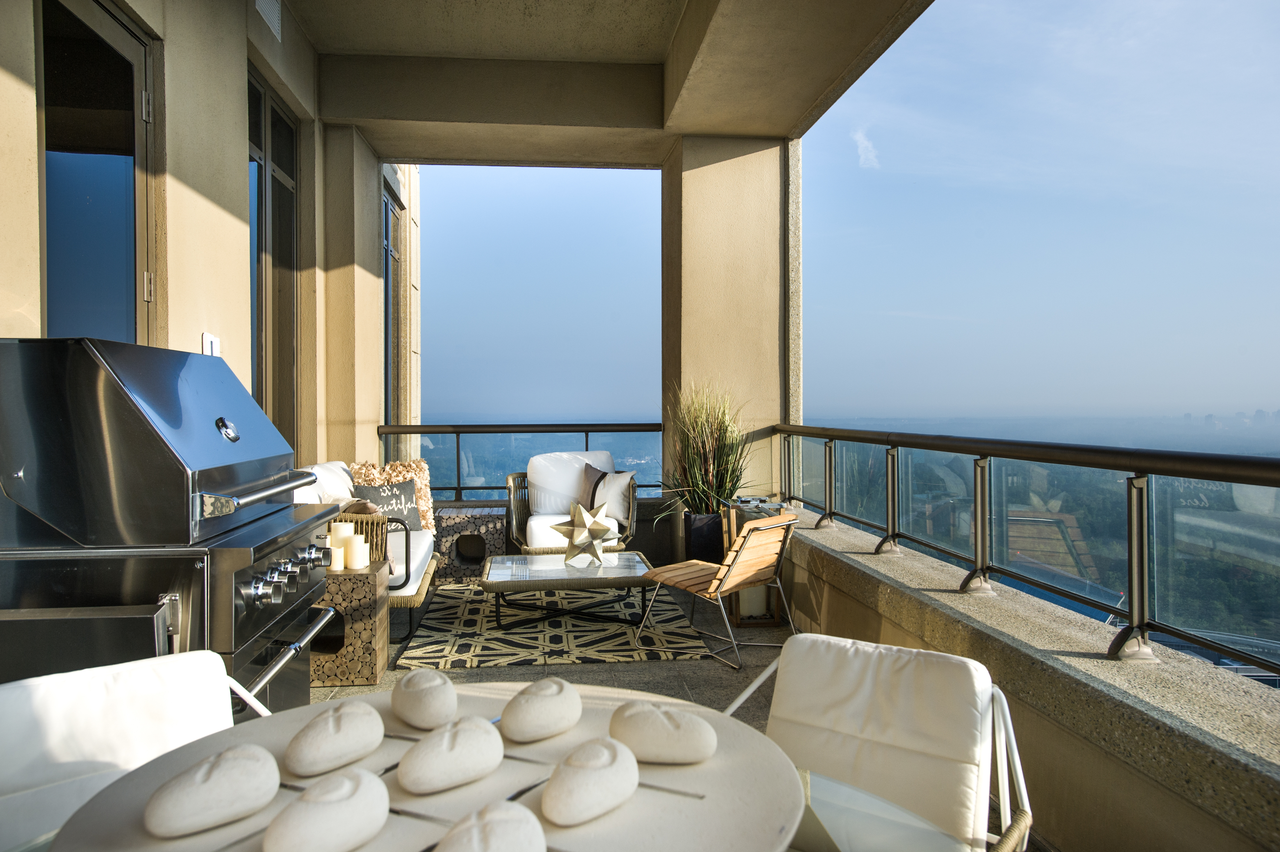 The outdoor lounge is furnished with an all-weather sofa, marble coffee table, stainless grill and glass-topped dining suite. The amazing view comprises the Atlanta skyline and Stone Mountain.(Photo: Business Wire)