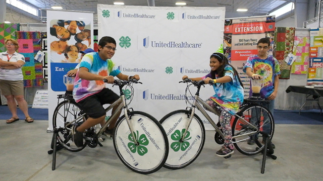 """Kevin Perez, Jodi Morales, Heydy Benitez, and Noah Beedles - 5th graders from Platte Valley Elementary School in Grand Island - create their own healthy smoothies on the UnitedHealthcare and 4-H smoothie bike at the Nebraska State Fair Thursday, Aug. 28, in Grand Island, Neb. The healthy-smoothie bikes are part of 4-H and UnitedHealthcare's """"Eat4-Health"""" partnership aimed at tackling obesity by promoting healthy eating and lifestyles among children and families (Video by Chad Greene)."""