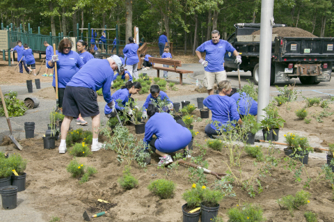 Canon employees, friends and family work together to plant new flowers. (Photo: Business Wire)
