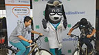 (L-R) Jovannie Rancheria (11) and Aaron Cruz (13) from Pategonia Montessori School are cheered on at the Santa Cruz County Fair in Sonoita by UnitedHealthcare mascot Dr. Health E. Hound and fellow students, as they make their own healthy smoothies on new blender bikes donated to Arizona 4-H as part of a $40,000 grant from UnitedHealthcare (Video: Espe Greenwood).