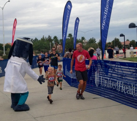 Young athletes cross the finish line with UnitedHealthcare mascot Dr. Health E. Hound at the 2013 Un