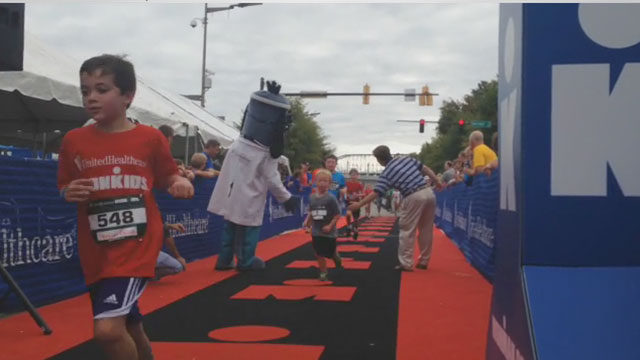 U.S. Congressman Chuck Fleishmann and UnitedHealthcare mascot Dr. Health E. Hound give high-fives to athletes as they finish their quest to become IRONKIDS at the UnitedHealthcare Chattanooga Fun Run. Source: Kevin Herglotz