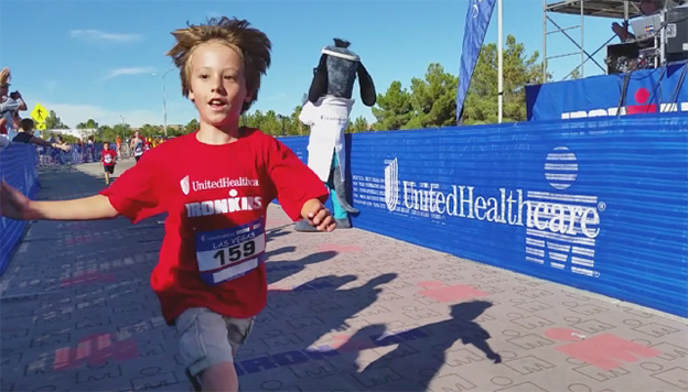 """UnitedHealthcare mascot Dr. Health E. Hound is pictured at the finish line of the UnitedHealthcare IRONKIDS Las Vegas Fun Run at Henderson Pavilion. More than 200 youth participated in today's race for """"triathletes to be."""" (Video credit: Kin Lui)"""