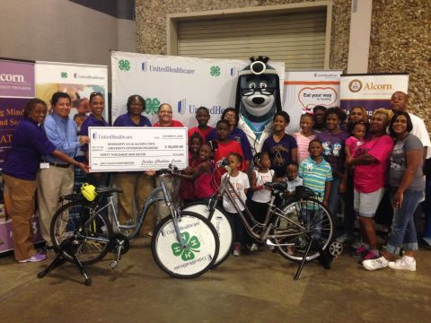 Mississippi 4-Hers celebrate a $40,000 grant from UnitedHealthcare to support their Eat4-Health partnership. This is the fourth year UnitedHealthcare has partnered with Mississippi 4-H and Alcorn State University Extension to promote healthy living among youth. As part of the program, UnitedHealthcare donated specially made blender bikes so kids can learn to make healthy snacks in a fun, energetic way. Pictured (2nd to Left): Richard Flores, Chief Operating Officer of UnitedHealthcare Community Plan of Mississippi, presenting the check to Mississippi 4-H leaders and youth along with UnitedHealthcare mascot Dr. Health E. Hound (Photo: Kevin Herglotz).