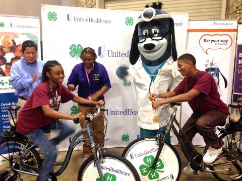 Caterina Harkins (L) of Starkville joins fellow Mississippi 4-Her Kendrick Lowery (R) of Crawford in making healthy smoothies with specially-made blender bikes donated to Mississippi 4-H by UnitedHealthcare. The donation is part of a $40,000 grant by UnitedHealthcare announced today that will promote healthy living among youth. The new smoothie bikes were unveiled during 4-H Day at the State Fair, where more than 100 fairgoers used a little sweat equity to make a healthy snack. Also in the photo (background): Richard Flores, Chief Operating Officer of UnitedHealthcare Community Plan of Mississippi; UnitedHealthcare mascot Dr. Health E. Hound; and Manola Erby, Mississippi 4-H Youth Specialist (Photo: Kevin Herglotz).