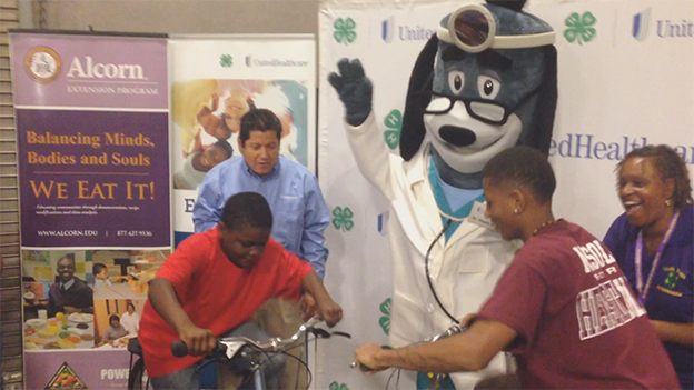 Cameron Brooks, 11, of Natchez (L) and Kendrick Lowery, 17, of Crawford make healthy smoothies on specially made bikes that blend healthy snacks by peddling. More than 100 young people made healthy smoothies at 4-H Day at the State Fair, where UnitedHealthcare announced a $40,000 donation to Mississippi 4-H and donated the bikes to be used throughout the state to promote healthy eating (Video: Kevin Herglotz).