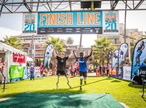 Rudy Garcia-Tolson and Marko Cheseto, two double amputees cross the finish line at the Aspen Medical Products San Diego Triathlon Challenge (Photo: Business Wire)