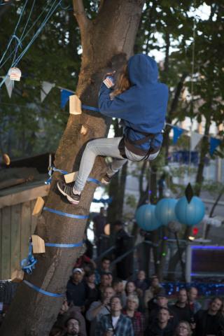 Bildunterschrift: Geld wächst doch auf Bäumen. Eine Besucherin des #MoneyTree-Events im Berliner IPSE Club klettert unter den Augen vieler Besucher und des Kamerateams zur Geldernte auf den großen MoneyTree.(Photo: Business Wire)