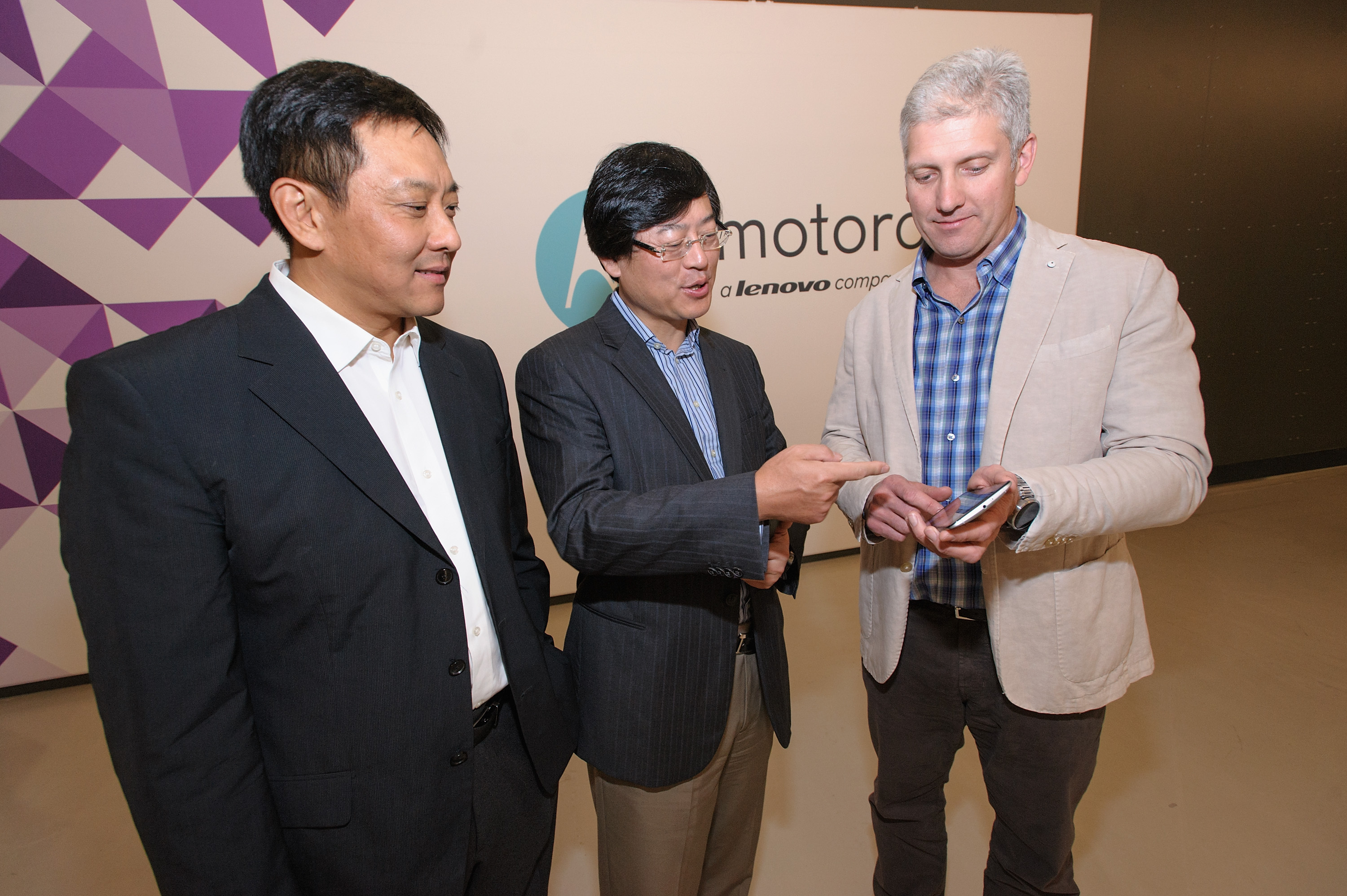 (from left to right) Liu Jun, EVP, Lenovo, President Mobile Business Group, Lenovo and Chairman of the Motorola Management Board; Yang Yuanqing, Lenovo Chairman and CEO; and Rick Osterloh, President and COO, Motorola Mobility celebrate the closing of Lenovo's acquisition of Motorola Mobility today. Here Rick Osterloh demonstrates the latest features of the new Nexus 6 smartphone in front of the company's new logo. (Photo: Business Wire)