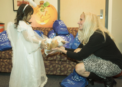 """UnitedHealthcare's Diana Marsh (right) shows Brooklyn of New Britain, Conn., a stuffed animal named Chewie, one of the fun items that are included in a """"Grins to Go"""" bag. Children from Connecticut Children's received """"Grins to Go"""" bags at a Halloween party. UnitedHealthcare Hartford employees were among volunteers from more than a dozen UnitedHealthcare offices nationwide who delivered 400 """"Grins to Go"""" bags to local children's hospitals and other youth-based organizations. The UnitedHealthcare Children's Foundation provides medical grants that help children gain access to health-related services not covered, or not fully covered, by their parents' commercial health insurance plan (Photo: Alan Grant, Digital Creations)."""