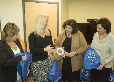 """UnitedHealthcare's Christine Kelly and Diana Marsh (left) and Maryellen Ciccio (right) share the contents of the UnitedHealthcare Children's Foundation """"Grins to Go"""" bag with Martha Schall, president, Connecticut Children's Medical Center Foundation. UnitedHealthcare Hartford employees were among volunteers from more than a dozen UnitedHealthcare offices nationwide who delivered 400 """"Grins to Go"""" bags to local children's hospitals and other youth-based organizations. The UnitedHealthcare Children's Foundation provides medical grants that help children gain access to health-related services not covered, or not fully covered, by their parents' commercial health insurance plan (Photo: Alan Grant, Digital Creations)."""