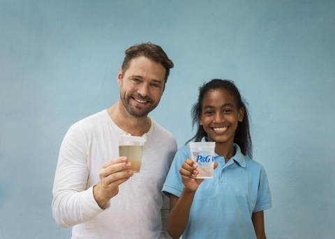 Jason Priestley and Alondra, from the Dominican Republic, hold the before and after of a cup of water purified with a P&G packet.(Photo: Business Wire)