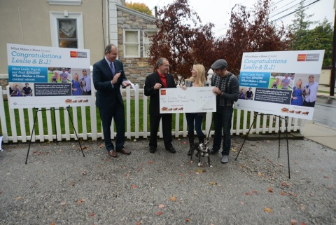 """Jim Linnane, Senior Vice President and Divisional Sales Manager with Wells Fargo Home Mortgage, and Rocco Tenaglia, Wells Fargo Home Mortgage Consultant, present Leslie Poprik and B.J. Capelli with a $250,000 check at their home in Ardmore, Pennsylvania. Leslie is the third winner of Wells Fargo's """"What Makes a Home"""" contest. The newlyweds made a video performing a song they wrote to answer the contest question, """"What makes a place feel like a home?"""" (Photo: Business Wire)"""