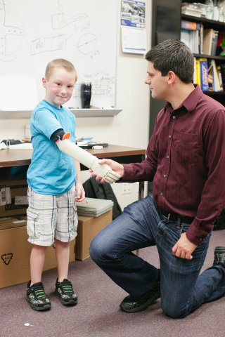 Alex shaking hands with Manero using his 3D printed robotic arm. (Photo: Kt Crabb Photography)
