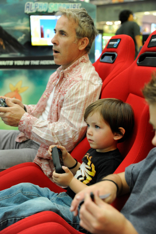 In this photo provided by Nintendo of America, Django F., 3, of Los Angeles races against his father Joseph F. and other attendees in Mario Kart 8 game on a giant HD TV screen at the Westfield Culver City mall in Los Angeles on Nov. 24, 2014. Throughout the Holiday season until Dec. 21, 2014, Nintendo is visiting 16 malls across the country to offer consumers a break from holiday shopping to play the season's must-have games for Wii U and Nintendo 3DS/2DS, including amiibo, Nintendo's new toys-to-life figures based on favorite video game characters including Mario, Donkey Kong and Pikachu. (Photo by Nintendo/Bob Riha, Jr.)