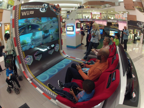 In this photo provided by Nintendo of America, fathers and sons race against each other in Mario Kart 8 on a giant HD TV screen at the Westfield Culver City mall in Los Angeles on Nov. 24, 2014. Throughout the Holiday season until Dec. 21, 2014, Nintendo is visiting 16 malls across the country to offer consumers a break from holiday shopping to play the season's must-have games for Wii U and Nintendo 3DS/2DS, including amiibo, Nintendo's new toys-to-life figures based on favorite video game characters including Mario, Donkey Kong and Pikachu. (Photo by Nintendo/Bob Riha, Jr.)