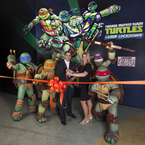 Official Ribbon Cutting to open Teenage Mutant Ninja Turtles Laser Lockdown at the Nickelodeon Suites Resort in Orlando. Louis Robbins from Nickelodeon Suites Resort and Kate Magnusson from  SimEx-Iwerks Entertainment. (Photo: Business Wire)