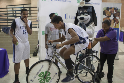 """Jenson Hooper (13) from West Briar Middle School in Houston is cheered on by UnitedHealthcare mascot Dr. Health E. Hound and teammates (l-r) Johnny Garcia and Cameron Dorsey along with Prairie View A&M Extension Program Health Coordinator Dawn Purton, as he uses a smoothie bike to create his own healthy snack in return for a little """"sweat equity."""" The smoothie bike is part of $40,000 grant announced today from UnitedHealthcare to Prairie View A&M Extension Program that will promote healthy living among youth. The grant announcement was made during the Ralph Cooper """"Stars of the Future Basketball Tournament"""" at Chavez High School in Houston. (Photo: Stephen Gutierrez)"""
