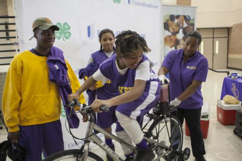 """Trey Bibbins (13) from Key Middle School in the 5th Ward is cheered on by teammates and Prairie View A&M Extension Program Health Coordinator Dawn Purton, as he uses a smoothie bike to create his own healthy snack in return for a little """"sweat equity."""" The smoothie bike is part of $40,000 grant announced today from UnitedHealthcare to Prairie View A&M Extension Program that will promote healthy living among youth. The grant announcement was made during the Ralph Cooper """"Stars of the Future Basketball Tournament"""" at Chavez High School in Houston. (Photo: Stephen Gutierrez)"""