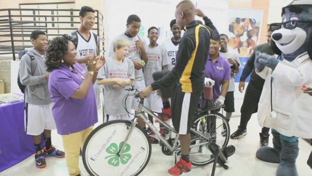 """Trey Tay (15) is cheered on by (left) Jacquelyn White, program leader FCS at Prairie View A&M Cooperative Extension Program, and teammates from West Briar Middle School as he uses a smoothie bike to create his own healthy snack in return for a little """"sweat equity."""" The smoothie bike is part of $40,000 grant announced today from UnitedHealthcare to Prairie View A&M Extension Program that will promote healthy living among youth. The grant announcement was made during the Ralph Cooper """"Stars of the Future Basketball Tournament"""" at Chavez High School in Houston. (Photo: Stephen Gutierrez)."""