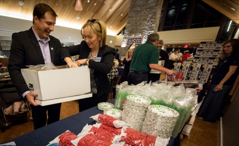 "Christian Kuhn and volunteers from local Homewood Suites by Hilton properties help construct ""Make a Moment"" boxes to be delivered to 10 USO centers across the country to help recreate special events for military families (Photo: Business Wire)"