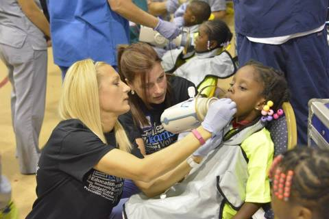 Preferred Dental Group team of Viki and Elise working with one of the Detroit TeamSmile children. (Photo: Business Wire)