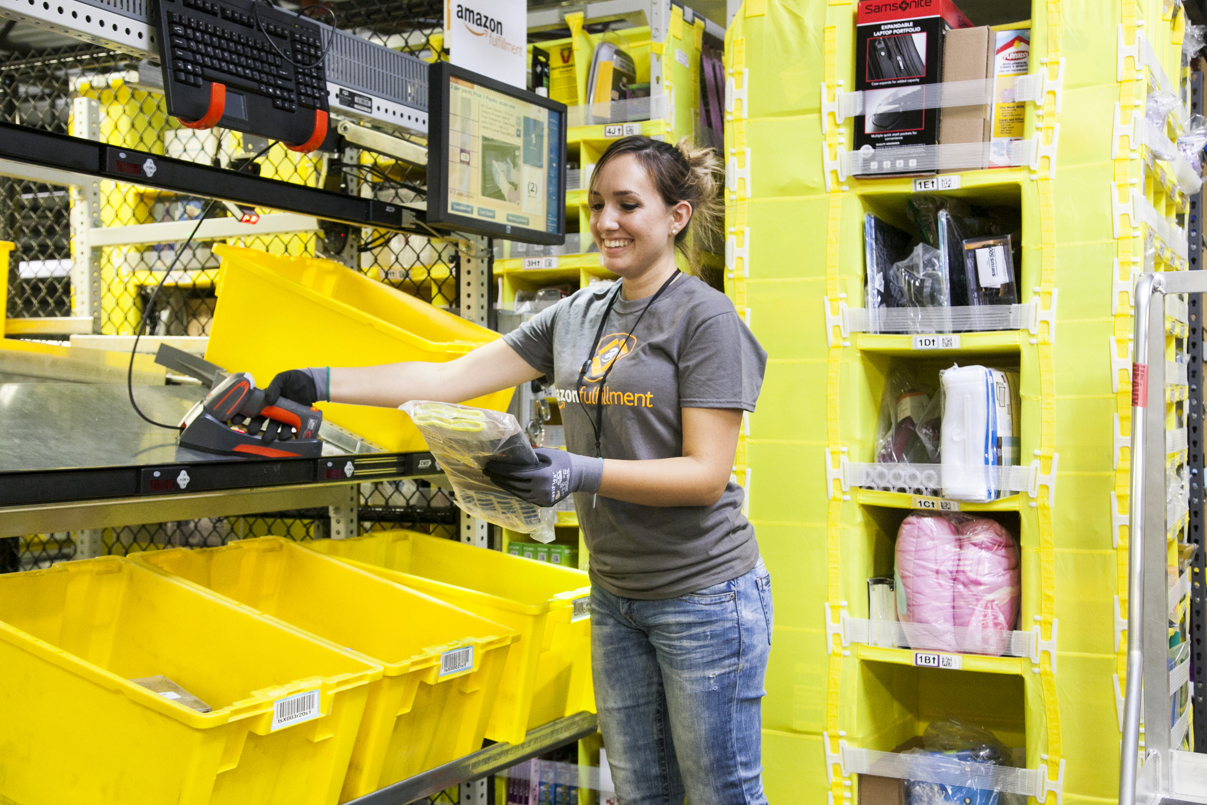 An Amazon employee picks items in the company's newest generation fulfillment center. (Photo: Business Wire)