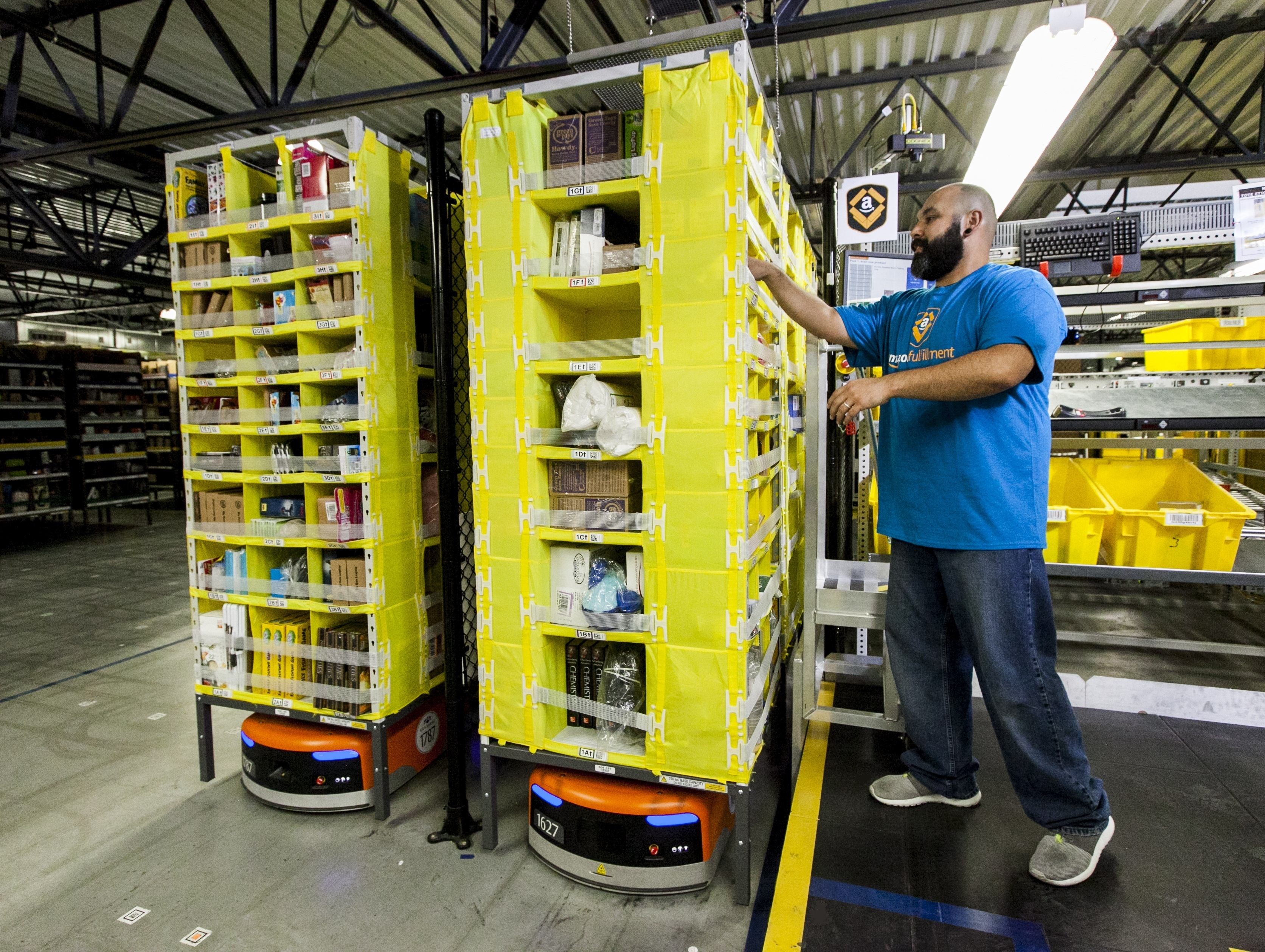 An Amazon employee picks items from a Kiva robot. (Photo: Business Wire)