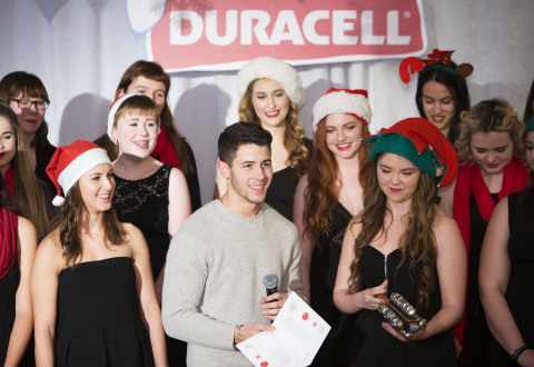 "Nick Jonas carols with the Etobicoke School of the Arts Women's Chorus at The Hospital for Sick Children (SickKids) in Toronto to celebrate the launch of the Duracell ""Powering Holiday Smiles"" program. For every pack of Duracell Quantum or CopperTop batteries purchased at Walmart Canada from December 1st to December 31st 2014, Duracell will donate 20 cents to Children's Miracle Network, with the goal to raise $150,000. (Photo: Business Wire)"