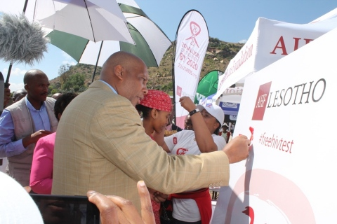 His Majesty King Letsie III places a red ribbon on AHF's commemorative pin board during a World AIDS ...