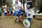 """UnitedHealthcare's mascot Dr. Health E. Hound cheers on Alachua County 4-H Members as they use a smoothie bike to create their own healthy snack in return for a little """"sweat equity"""" at the annual """"Little Run on the Prairie"""" 5K race at Payne's Prairie Preserve State Park in Micanopy, FL. The smoothie-bike is part of $40,000 grant announced today from UnitedHealthcare to University of Florida's Institute of Food and Agricultural Sciences (IFAS) that will promote healthy living among youth. (Photo credit: Julie Brewer Photography)"""