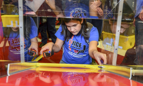 Student takes measurements of the playing field following the reveal of the 2015 FIRST® Robotics Competition RECYCLE RUSH game. (Photo: Business Wire)