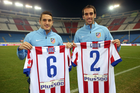 Atletico Madrid players, Koke and Diego Godin, display the new club shirt with the Plus500 logo. (Ph ...