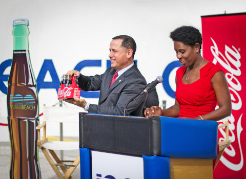 Melanie Jones, General Manager for Coca-Cola South Florida, present Miami Beach Mayor Philip Levine the first Miami Beach 100th Anniversary Commemorative Coca-Cola six-pack. (Photo: Business Wire)