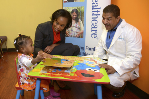 At the Southside Medical Center in Atlanta, 18-month-old Dakota Lemons is being read one of the new Sesame Street books by Jocelyn Chisholm Carter of UnitedHealthcare and David Williams, M.D., President and CEO of Southside Medical Center. Dakota is using one of the newly donated Sesame Street reading corners by UnitedHealthcare to 14 Federally Qualified Health Centers (FQHC) throughout the state. The donations are part of UnitedHealthcare's Healthy Habits for Life partnership with Sesame Workshop (Photo: Windgate Downs).