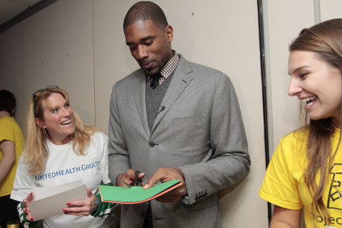 """Boston Celtics Legend Leon Powe (center) joined Karen McMullen from UnitedHealth Group (left) and Melody Eaton of Project Sunshine (right) to create arts & crafts kits. More than 100 volunteers from UnitedHealth Group created and assembled 1,000 Project Sunshine Creative Arts & Craft Kits, which contain educational and entertaining crafts to provide children facing significant medical challenges some much-needed fun. This """"Sending Sunshine"""" event is one of several programs that Project Sunshine has created to help children be children while they are undergoing medical care. (PHOTO: Matthew Healey)"""