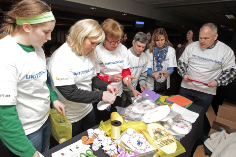 """More than 100 volunteers from UnitedHealth Group, including Lenny Driscoll (right), Kerry Armstrong (second from right) and Roberta Dunn Tracy (second from left) and their families, created and assembled 1,000 Project Sunshine Creative Arts & Craft Kits, which contain educational and entertaining crafts to provide children facing significant medical challenges some much-needed fun. This """"Sending Sunshine"""" event is one of several programs that Project Sunshine has created to help children be children while they are undergoing medical care. (PHOTO: Matthew Healey)"""