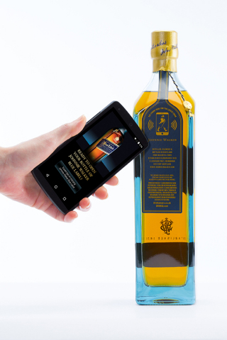 "NFC-enabled smartphone reading the tag on a JOHNNIE WALKER BLUE LABEL® ""smart bottle"" prototype. (Photo: Business Wire)"