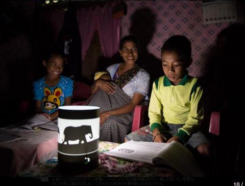 象をデザインしたシェード付きソーラーランタンの明かりで読書する子どもたち (写真:ビジネスワイヤ)