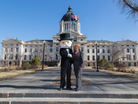 MR. MONOPOLY and Pierre Mayor Laurie Gill stand in front of the South Dakota State Capitol, Pierre SD. Pierre received the most votes in the MONOPOLY HERE & NOW property space vote and will be featured as the iconic Boardwalk space in the upcoming MONOPOLY HERE & NOW: U.S. Edition game. Photo by Patrick M Callahan, 2015. Released.