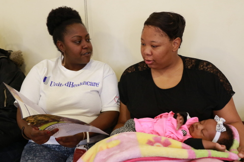 Mercedes Carr, left, hands a brochure explaining the benefits of UnitedHealthcare's BabyBlocks® an online, interactive incentive program that helps moms receive better pre- and postnatal care, keep health-baby appointments and maintain healthy behaviors throughout pregnancy to Shamir Croom and her god daughter Makayla McQueen (2 mo.) during the Citywide Baby Shower in Youngstown, OH for expectant moms and new parents hosted by UnitedHealthcare and the City of Youngstown Office on Minority Health. (Photo Credit: Emmett King)