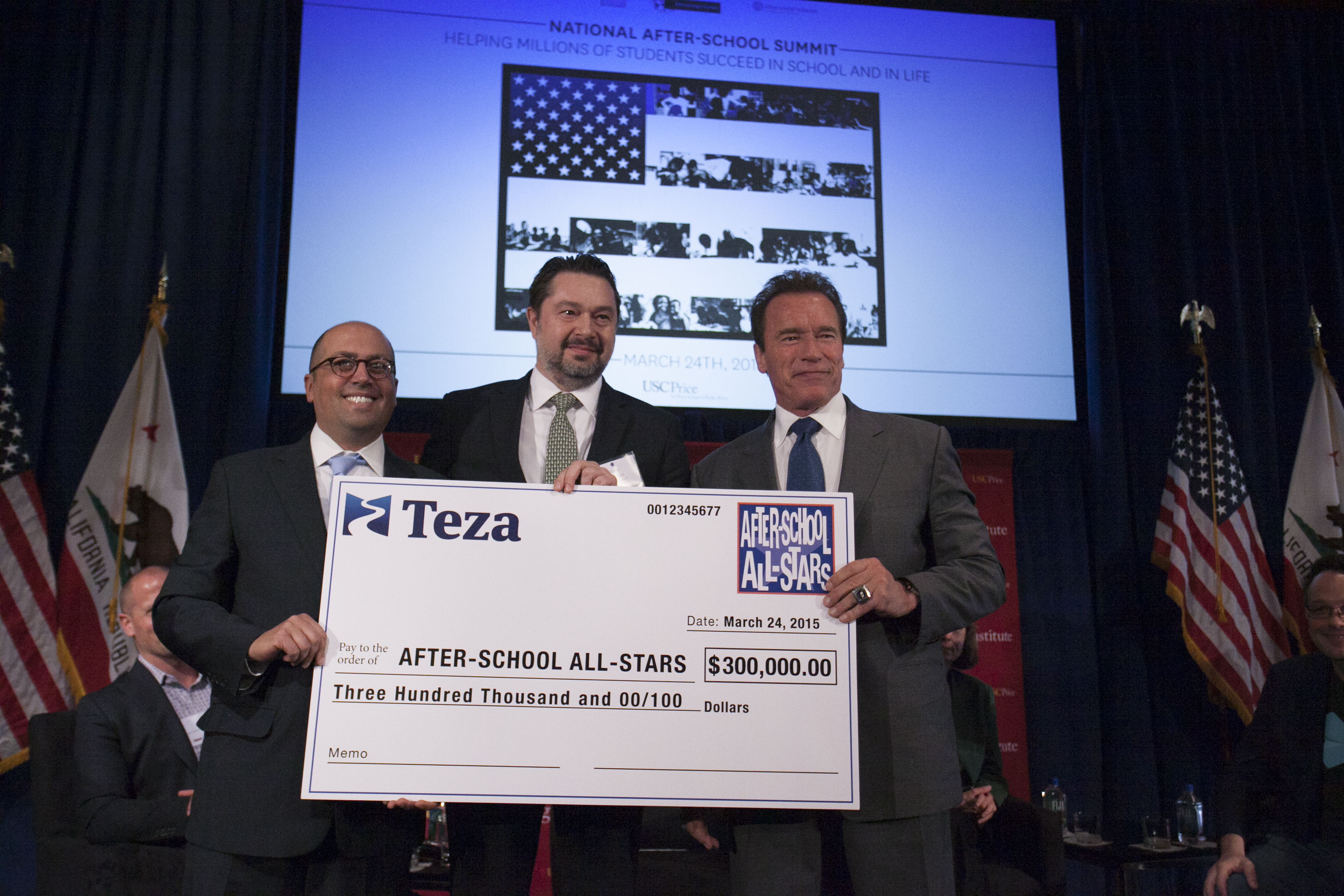 Misha Malyshev presents check to After-School All-Stars. From left: Ben Paul for ASAS, Misha Malyshev for Teza Technologies and Arnold Schwarzenegger. (Photo: Business Wire)