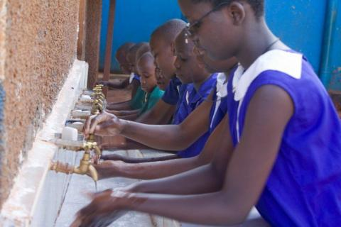 Children wash their hands before class begins at a school in Uganda. (Photo: Business Wire)