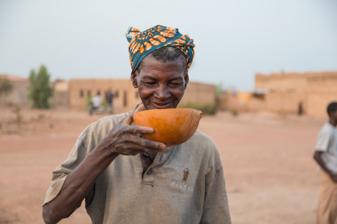 A woman drinks safe water from a RAIN project in her village outside Ouagadougou, Burkina Faso. (Photo: Business Wire)