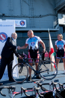 Dr. John Mateczun, president, UnitedHealthcare Military & Veterans, presents a bike to Retired Marine Corps Staff Sergeant Alex Victorino at a ceremony this morning on the U.S.S. Midway Flight Deck. UnitedHealthcare presented 16 replacement bikes to Ride 2 Recovery's Project HERO Balboa group, of which Victorino has been a participant since 2013. To his left is Jamie Rihn, Ride 2 Recovery's Project HERO Balboa coordinator (Photo: Wally Nell).