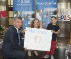 """Pam Keough, president and CEO of Make-A-Wish Connecticut and Jim Bedard, CFO of UnitedHealthcare's Northeast Region, present Louis, age 5, with a poster made by UnitedHealthcare commemorating his Make-A-Wish trip to Florida to swim with dolphins. UnitedHealthcare employees raised more than $16,000 through a statewide two-week employee """"lights of hope"""" gift campaign to help Make-A-Wish of Connecticut grant wishes to children with life-threatening medical conditions. Today marks the 35th anniversary of the founding of Make-A-Wish. The Connecticut chapter has made more than 2,500 wishes come true since its inception in 1986 (Photo: Digital Creations, Alan Grant)."""